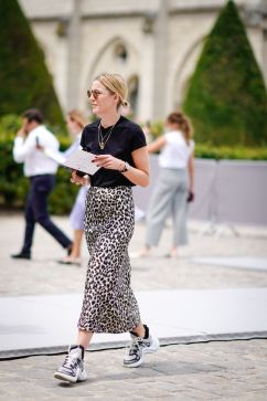PARIS, FRANCE - JULY 02: A guest wears a black t-shirt, sunglasses, a necklace, a leopard print skirt , Vuitton sneakers shoes, outside Dior, during Paris Fashion Week Haute Couture Fall Winter 2018/2019, on July 2, 2018 in Paris, France. (Photo by Edward Berthelot/Getty Images)